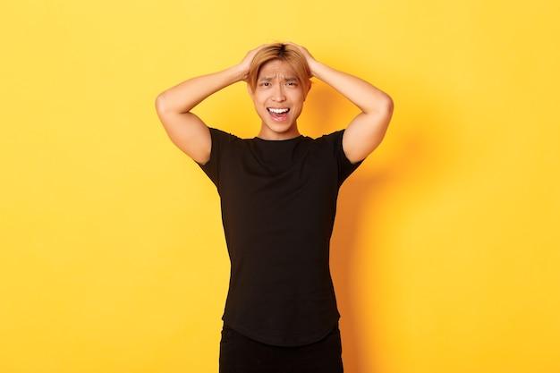 Porträt des jungen asiatischen kerls, der in panik gerät, ängstlich und verärgert aussieht, hände auf kopf hält und verzieht das gesicht, über gelber wand stehend