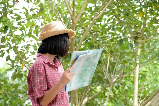 Porträt des jungen asiatischen mädchenreisenden, der karte hält