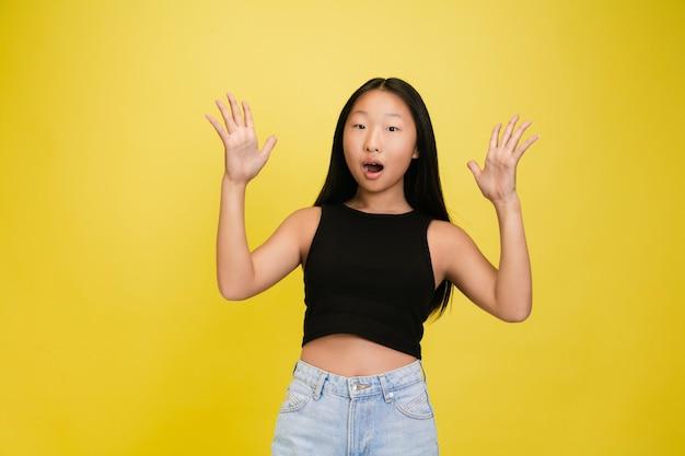 Porträt des jungen asiatischen mädchens lokalisiert auf gelb Premium Fotos