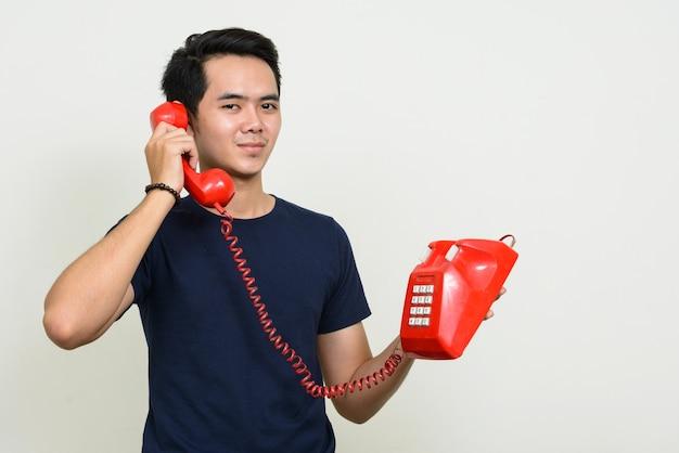 Porträt des jungen asiatischen mannes, der am alten telefon spricht