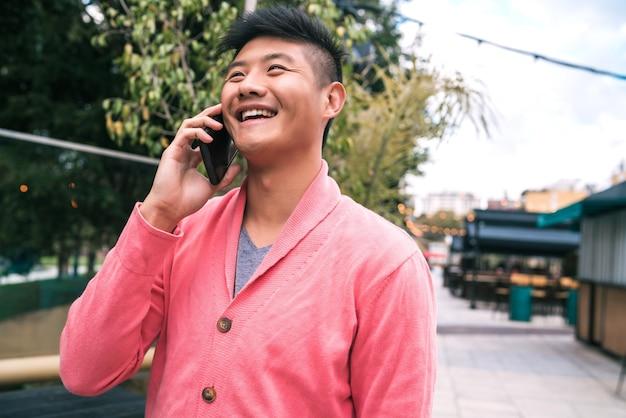 Porträt des jungen asiatischen mannes, der am telefon draußen in der straße spricht. kommunikationskonzept.