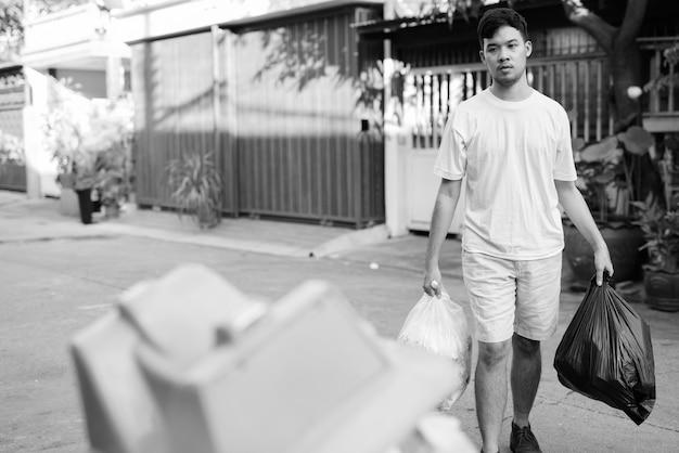 Porträt des jungen asiatischen mannes, der den müll zu hause herausnimmt