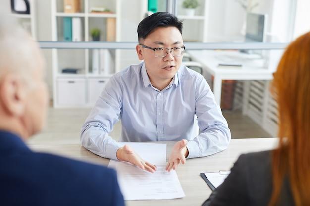 Porträt des jungen asiatischen mannes, der fragen während des vorstellungsgesprächs beantwortet, das gegenüber zwei personalmanagern sitzt, kopienraum