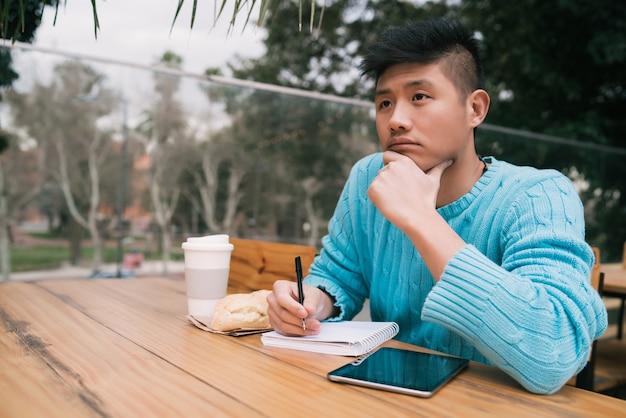 Porträt des jungen asiatischen mannes, der mit seinem digitalen tablett studiert und einige notizen macht, während er in einem café sitzt. technologiekonzept.