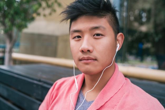Porträt des jungen asiatischen mannes, der musik mit kopfhörern beim sitzen auf einer bank in einem park hört.