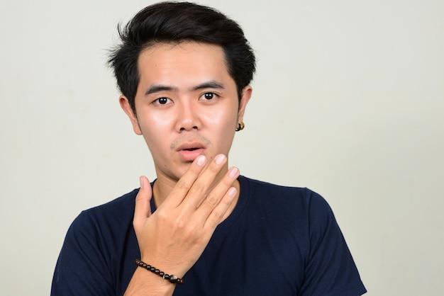 Porträt des jungen asiatischen mannes, der schockiert schaut