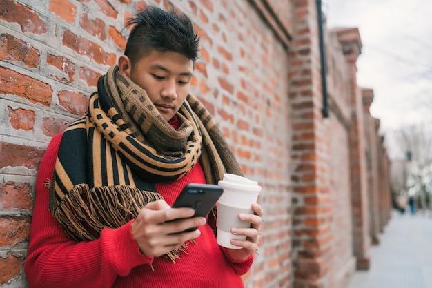 Porträt des jungen asiatischen mannes, der sein handy benutzt, während er eine tasse kaffee hält und draußen auf der straße steht