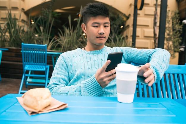 Porträt des jungen asiatischen mannes, der sein handy benutzt, während er in einem café sitzt.