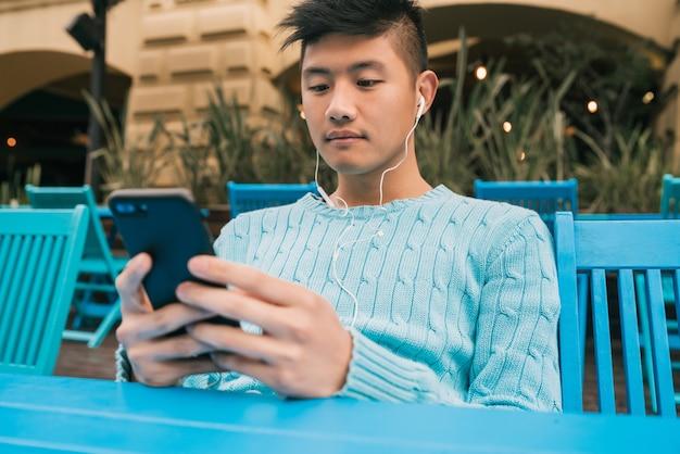 Porträt des jungen asiatischen mannes, der sein handy mit kopfhörern beim sitzen in einem café verwendet. kommunikationskonzept.