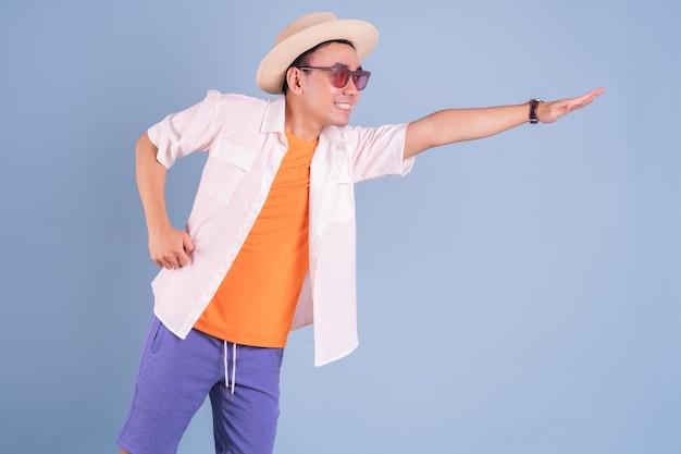 Porträt des jungen asiatischen mannes, der sommerkleidung auf blauem hintergrund trägt