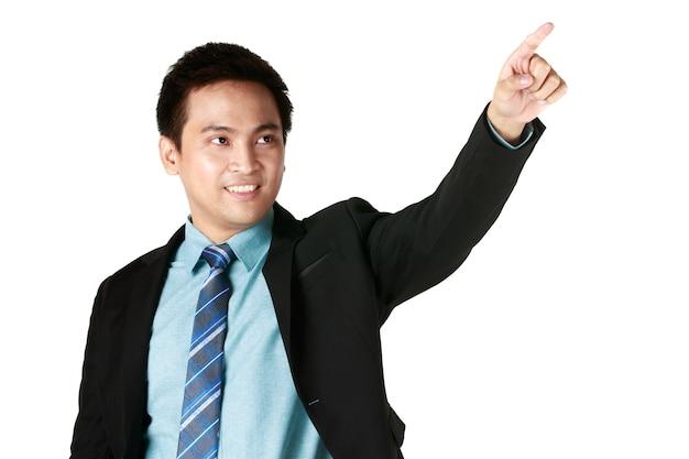 Porträt des jungen asiatischen mannes, der stehend mit schwarzem anzug lächelt und fingerzeig in weißem hintergrund zeigt. konzeptgeschäftsmann-erfolgskopienraum.