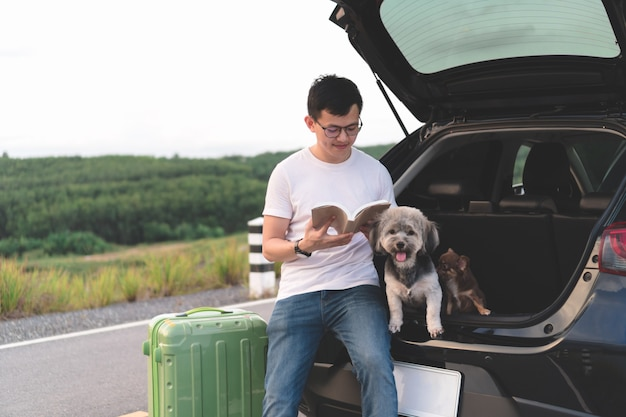 Porträt des jungen asiatischen mannlesebuches beim sitzen im offenen stamm des autos mit seinen hunden.