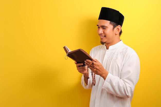 Porträt des jungen asiatischen muslimischen mannes, der den koran auf gelb liest