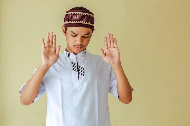 Porträt des jungen asiatischen muslimischen mannes salat mit dem heben seiner hand oder takbiratul ihram