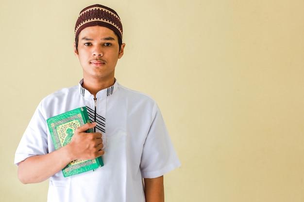 Porträt des jungen asiatischen muslims, der das heilige buch alquran hält
