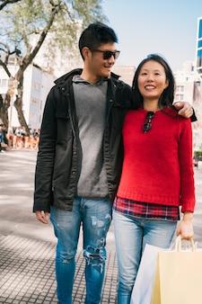 Porträt des jungen asiatischen paares in der liebe, die in der stadt nach dem einkaufen geht. shop-konzept.