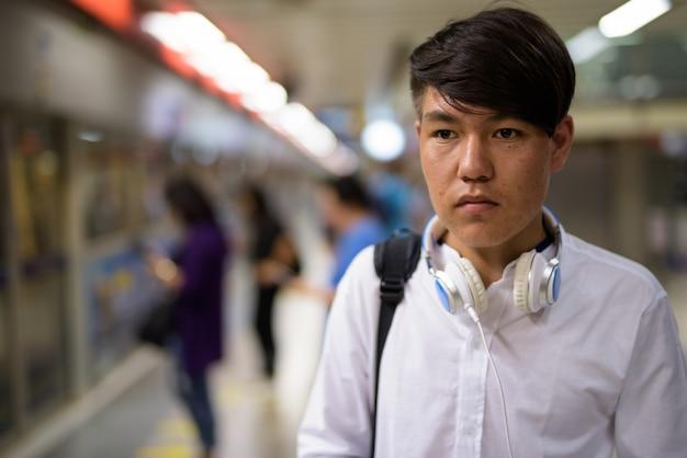 Porträt des jungen asiatischen teenagers, der auf den zug an der u-bahnstation von bangkok, thailand wartet