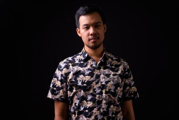 Porträt des jungen asiatischen touristenmannes mit böhmischem hemd auf schwarzem