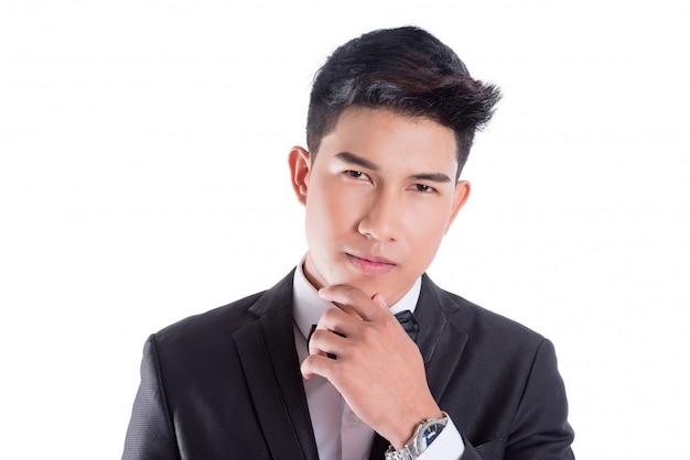 Porträt des jungen asiatischen überzeugten mannes kleidete im smoking mit der fliege an, die auf weißem hintergrund lokalisiert wurde