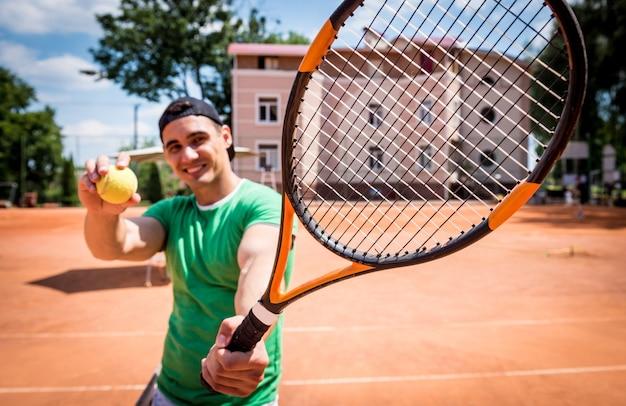 Porträt des jungen athletischen mannes auf tennisplatz