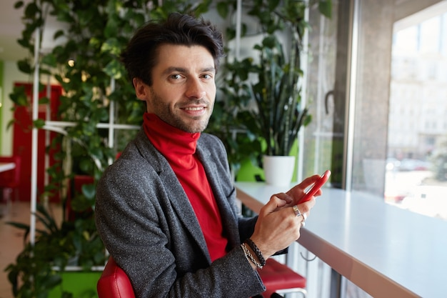 Porträt des jungen attraktiven braunhaarigen bärtigen mannes, der smartphone in der erhöhten hand hält und gern kamera mit hellem lächeln betrachtet, lokalisiert über stadtcaféinnenraum
