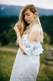 Porträt des jungen attraktiven eleganten blonden mädchens im blauen romantischen kleid, das über landschaft aufwirft
