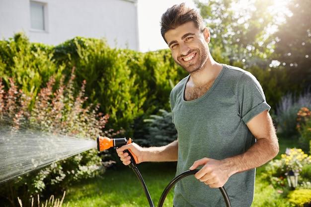 Porträt des jungen attraktiven freudigen floristen im blauen t-shirt, das mit zähnen lächelt, blumen im landhaus gießt, entspannende arbeit im sommermorgen tut.