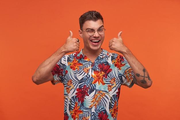 Porträt des jungen attraktiven fröhlichen kerls in der brille und im geblümten hemd, zeigt seegeste, sieht glücklich aus, steht über orange hintergrund und schaut in die kamera, zwinkert und breit lächelnd.