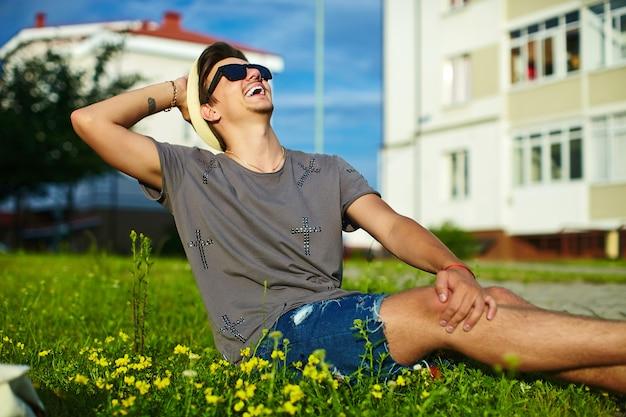 Porträt des jungen attraktiven modernen stilvollen mannes im lässigen stoff im hut in den gläsern, die im park im grünen gras sitzen