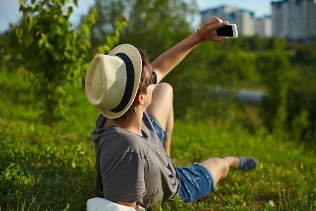 Porträt des jungen attraktiven modernen stilvollen mannes im zufälligen stoff im hut in den gläsern, die im park im grünen gras macht selfie sitzen