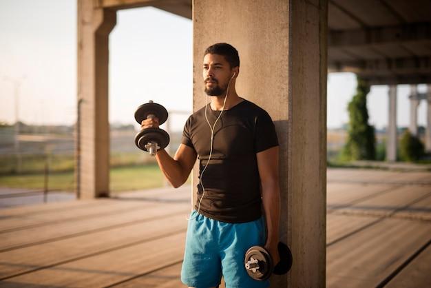Porträt des jungen attraktiven sportlers, der gewichte hebt und bizepsübung tut