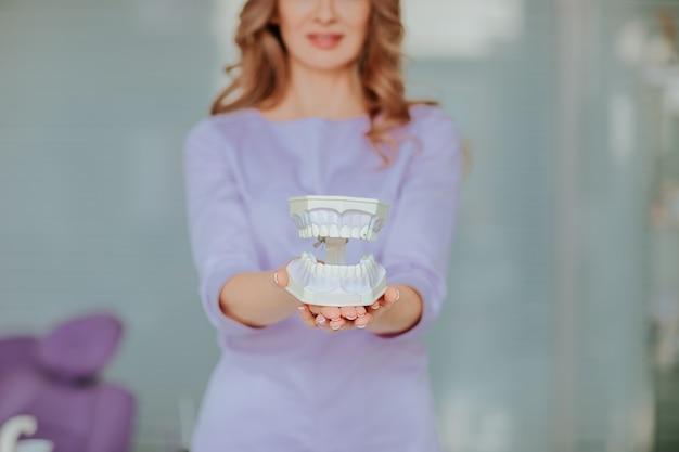 Porträt des jungen attraktiven zahnarztarztes mit dem langen lockigen haar in der violetten medizinischen uniform, die mit plastikmund im kabinett aufwirft.