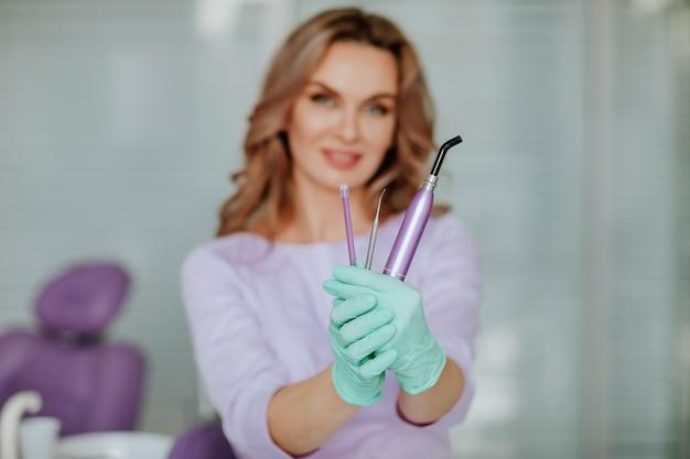 Porträt des jungen attraktiven zahnarztarztes mit dem langen lockigen haar in der violetten medizinischen uniform und den grünen medizinischen handschuhen, die mit werkzeugen im kabinett aufwerfen