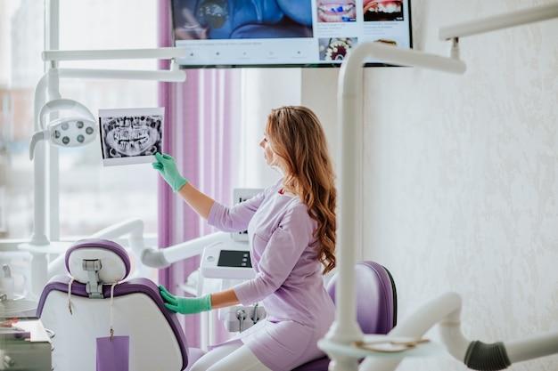 Porträt des jungen attraktiven zahnarztes mit langen lockigen haaren in violetter medizinischer uniform und grünen medizinischen handschuhen, die mit röntgenstrahl im kabinett aufwerfen.