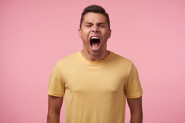 Porträt des jungen aufgeregten kurzhaarigen mannes mit dem kurzen haarschnitt, der sein gesicht runzelt, während er verrückt schreit und mit den händen nach unten gegen rosa hintergrund steht