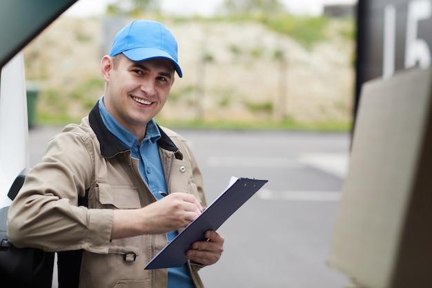 Porträt des jungen auslieferungsmannes, der dokumente ausfüllt und in die kamera lächelt, während er nahe am auto draußen steht
