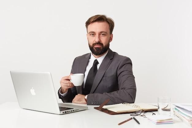 Porträt des jungen bärtigen brünetten mannes mit kurzem haarschnitt, der vorne mit ruhigem gesicht schaut, während er mit seinem laptop und notizbuch über weißer wand arbeitet und tasse tee hat