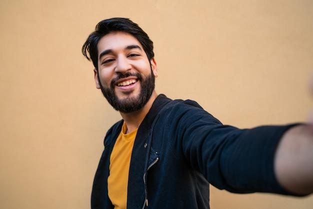 Porträt des jungen bärtigen hipster-mannes, der kamera betrachtet und ein selfie gegen gelb nimmt.