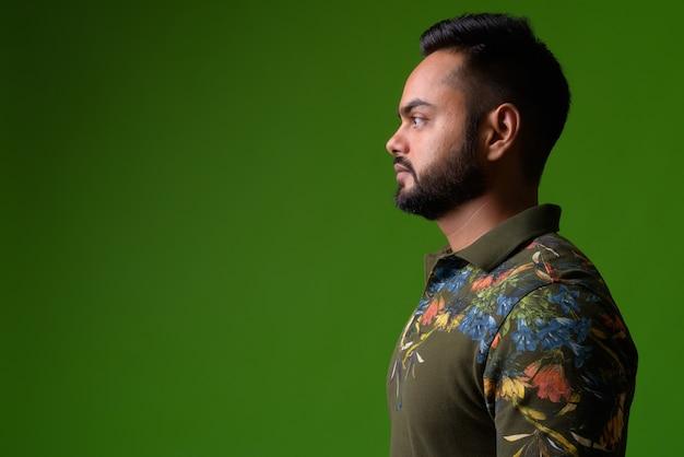 Porträt des jungen bärtigen indischen mannes auf grün