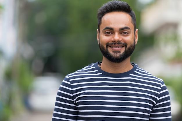 Porträt des jungen bärtigen indischen mannes in den straßen draußen