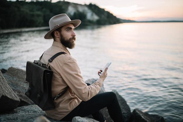 Porträt des jungen bärtigen mannes, der handy hält, bewundern sie schöne natur und sonnenuntergang. hübscher reisender, der hipsterhut und lederrucksack trägt, die am flussufer sitzen. zeit zu reisen konzept
