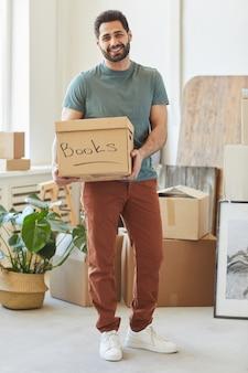 Porträt des jungen bärtigen mannes, der pappkarton mit büchern hält und lächelt, während er in seiner wohnung steht