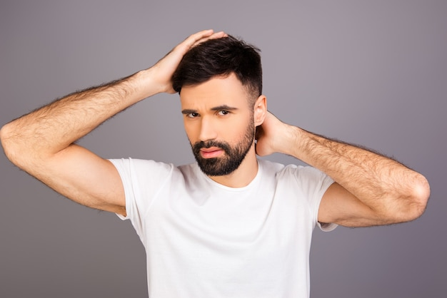 Porträt des jungen bärtigen mannes, der seine haare fachmännisch macht