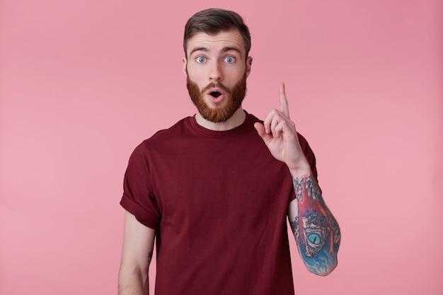 Porträt des jungen bärtigen mannes mit tätowierter hand, kam mit einer lösung für das problem, zeigt seinen zeigefinger nach oben hat die idee, dachte inspiration über rosa hintergrund isoliert.