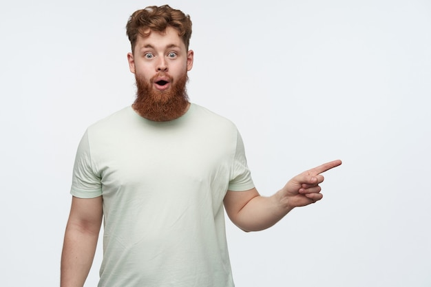Porträt des jungen bärtigen rothaarigen kerls, trägt leeres t-shirt, das mit einem finger auf den rechten kopierraum zeigt