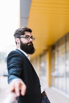 Porträt des jungen bartgeschäftsmannes mit den schwarzen brillen, die weg schauen