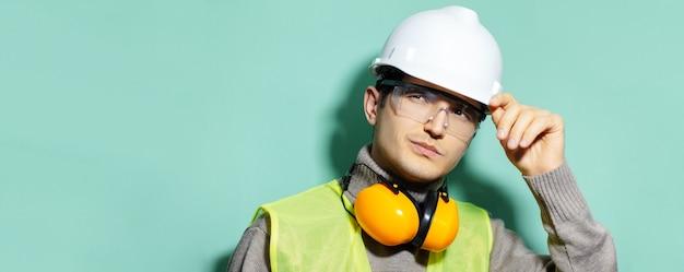 Porträt des jungen bauingenieurarbeiters, der schutzhelm, schutzbrille, jacke und kopfhörer auf hintergrund der aqua menthe farbe trägt.