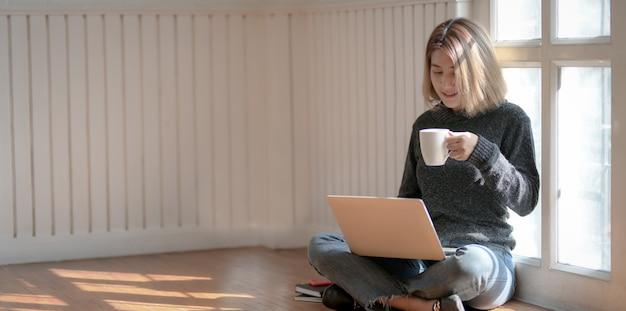 Porträt des jungen berufsfreiberuflers, der an ihrem projekt arbeitet und heißen kakao beim sitzen nahe den fenstern trinkt
