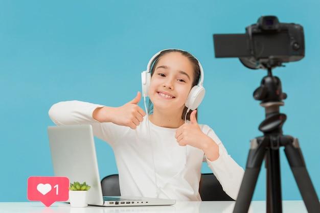 Porträt des jungen bloggers, der daumen hoch zeigt