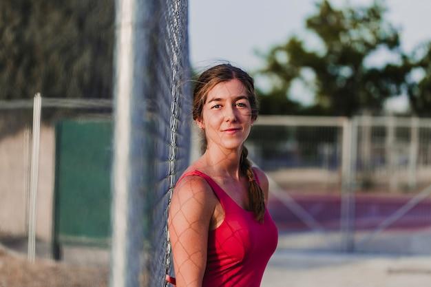 Porträt des jungen blonden eignungsfrauenläufers, der auf stadion bei sonnenuntergang sport und gesundes lebensstilkonzept sich entspannt